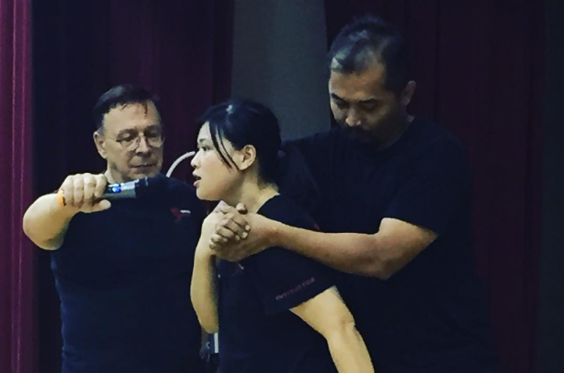 Demonstrating how to get out of a chokehold with a hammer strike to the groin